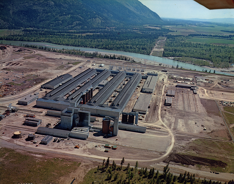 An aerial color photo, shows the plant from the north circa 1955 soon after it began operating, with the paste plant and storage silos in the foreground, four long potrooms, casting to the left, warehouse and machine shops to the right, offices and parking lot to the far right, the high voltage switchyard at the south end of the potlines, a cleared strip of land on the other side of the river for the BPA transmission lines from the Hungry Horse Dam and the Hot Springs. Photo from Archives and Special Collections, Mansfield Library, University of Montana