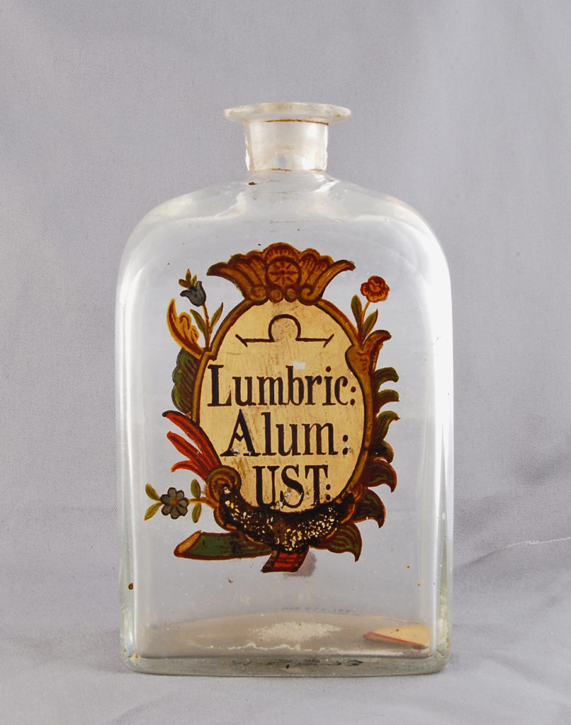 This square glass bottle is labeled Lumbric Alum UST with the alchemical symbol for Spirits. Lumbricor is dried and pounded earthworms, alum is potassium aluminum sulfate, and ustum is Latin for heated. The solution was often used as an emetic, astringent, or diuretic. Photo from the National Museum of American History, Kenneth E. Behring Center